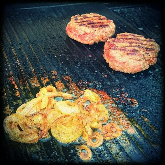 Burger patties and habanero-honey onion rings on the grill
