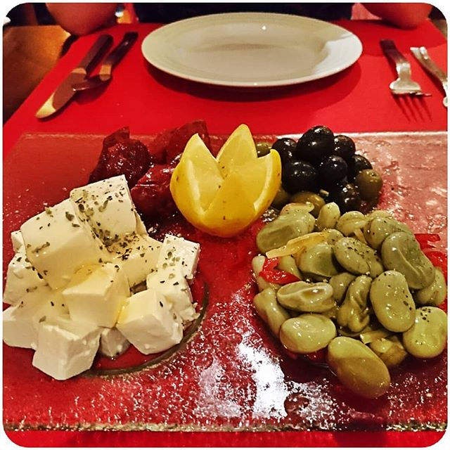 appetizer plate with olives, dried tomato,  feta cheese and beans